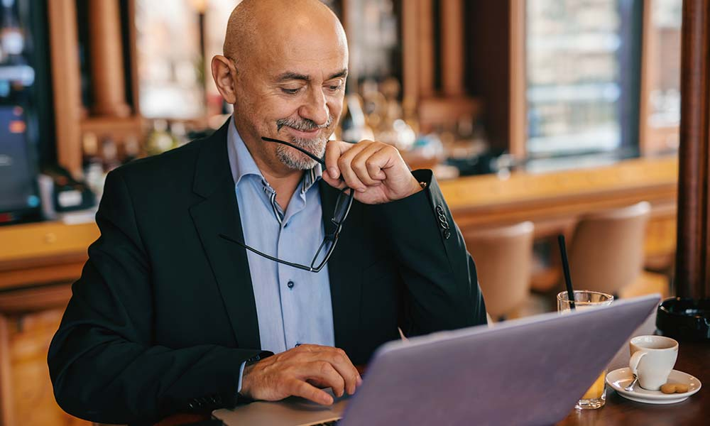 Baby boomer businessman in suit using his laptop
